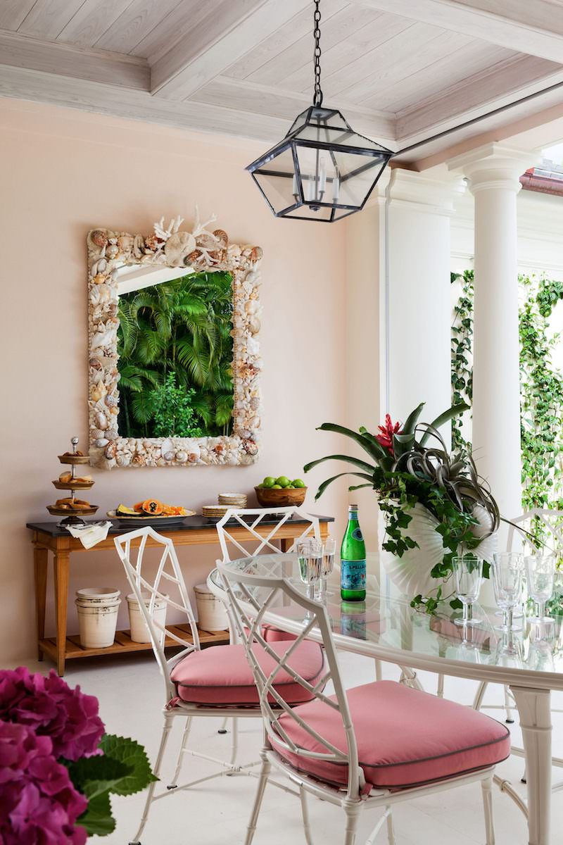 Dining room with white chairs pink cushions