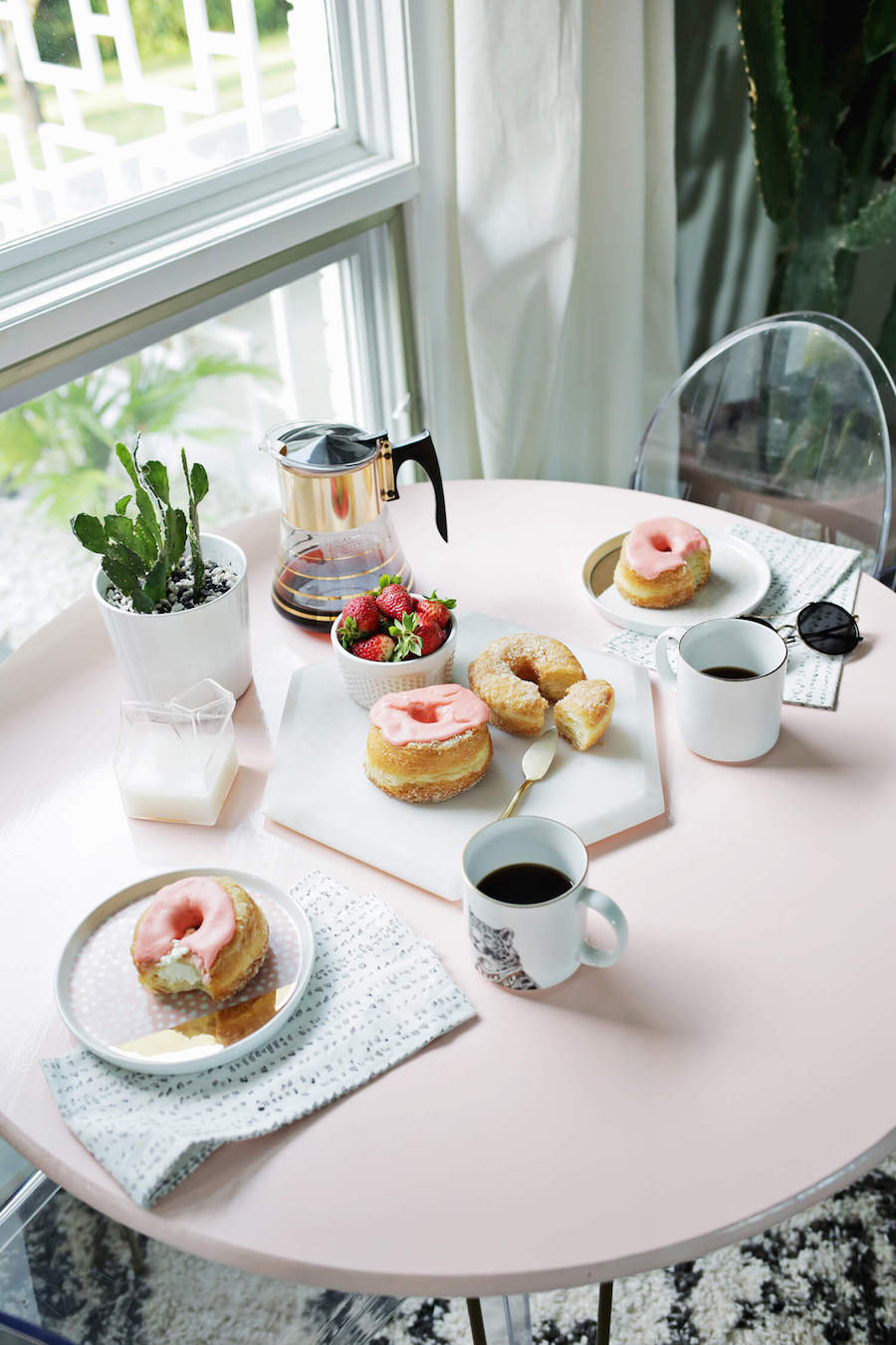 Donut breakfast on soft pink table