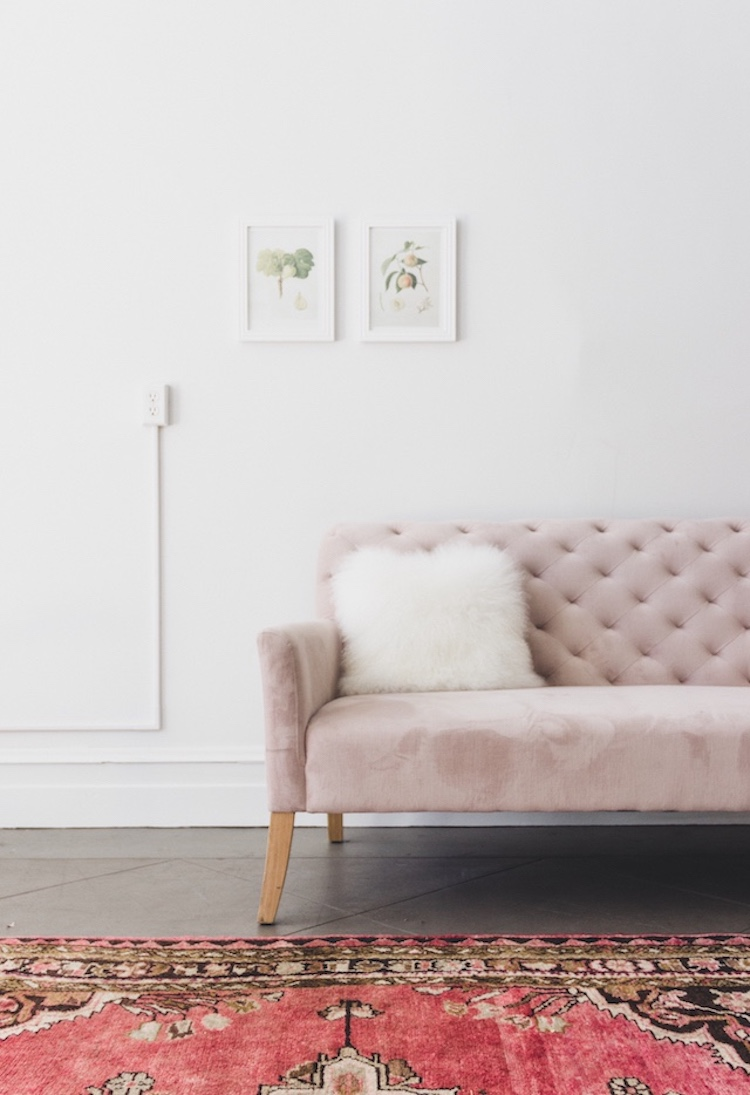 Dusty pink velvet tufted sofa with oriental rug