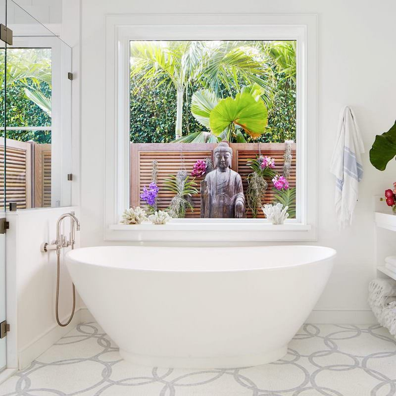 Freestanding tub with window overlooking garden