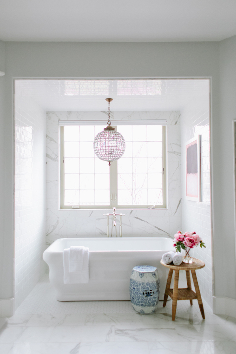 Freestanding white bathtub with crystal chandelier