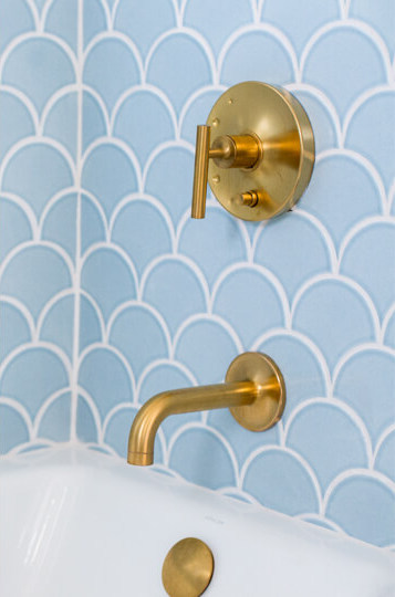 Gold Brass Faucet in bathtub with blue tiles