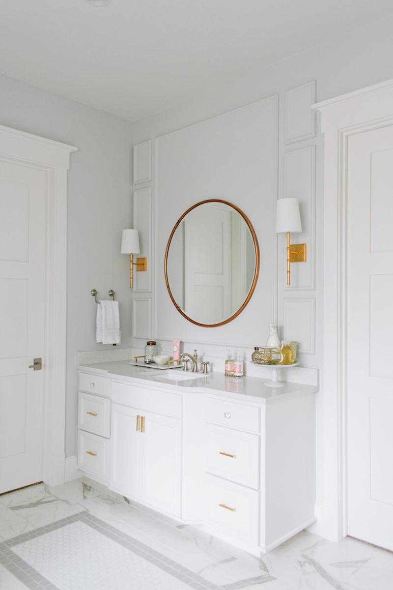 Gold circular mirror in white bathroom