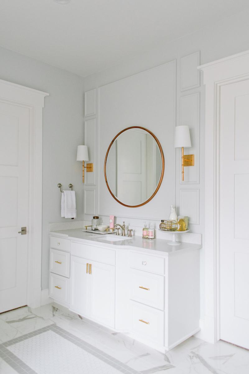 Gold circular mirror in white bathroom