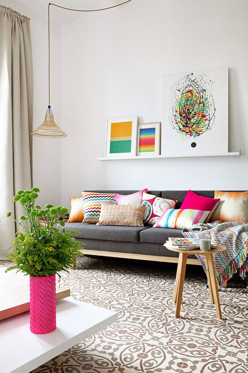 Grey couch in Barcelona apartment with multi-color throw pillows