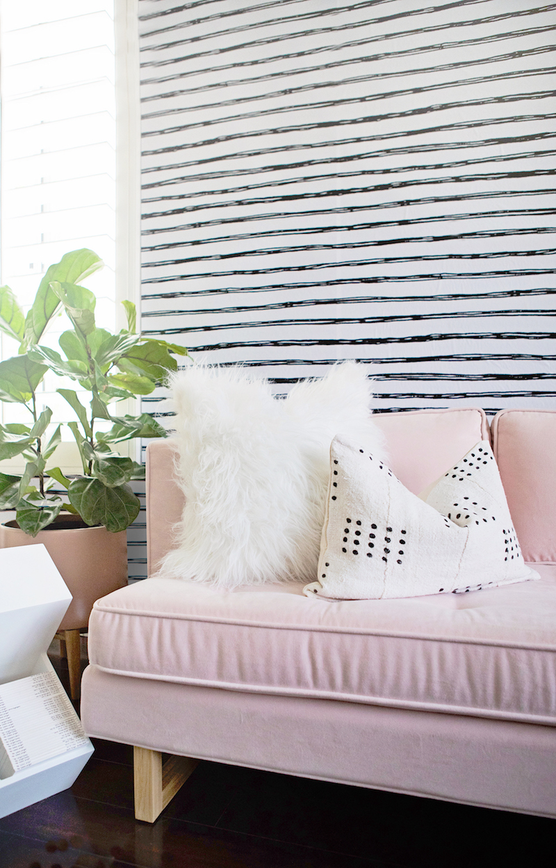 Light Pink sofa with wood feet and white fur pillow and striped wallpaper via Project Nursery