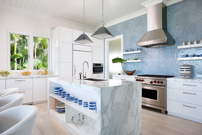 Marble kitchen island with blue tile backsplash