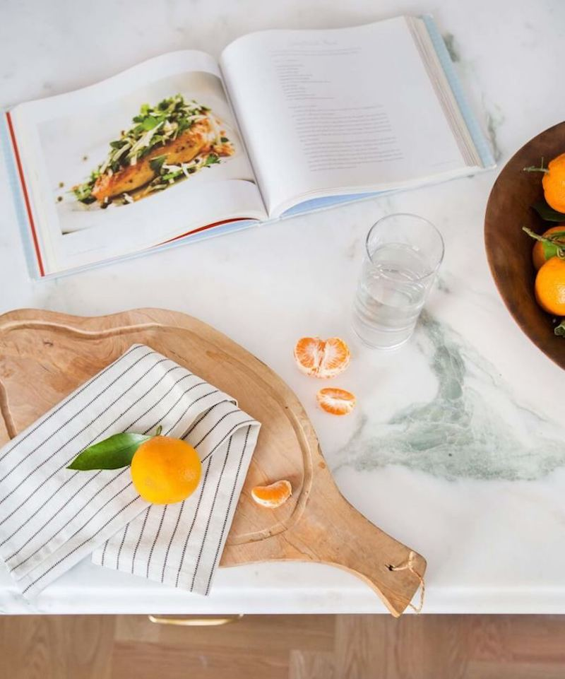 Natural wood cutting board on marble countertop via Emily Henderson