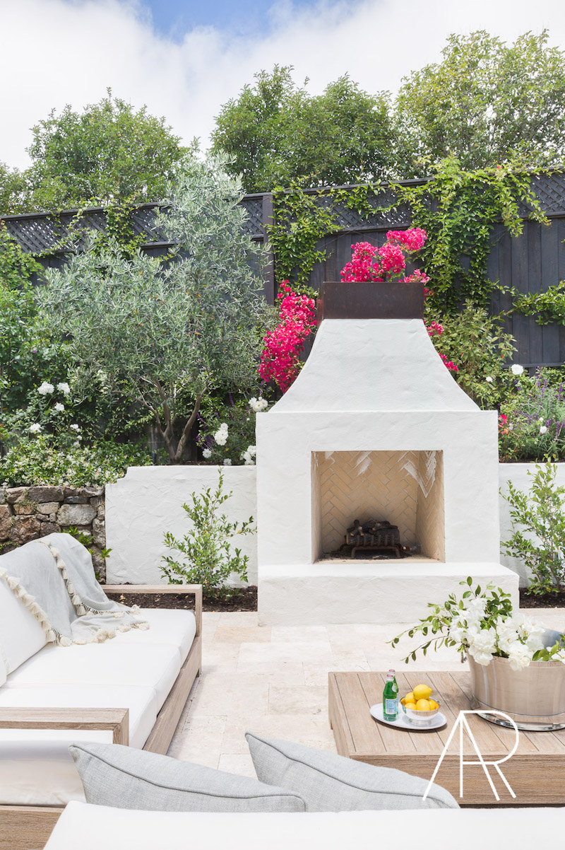 Outdoor beige fireplace with pink flowers