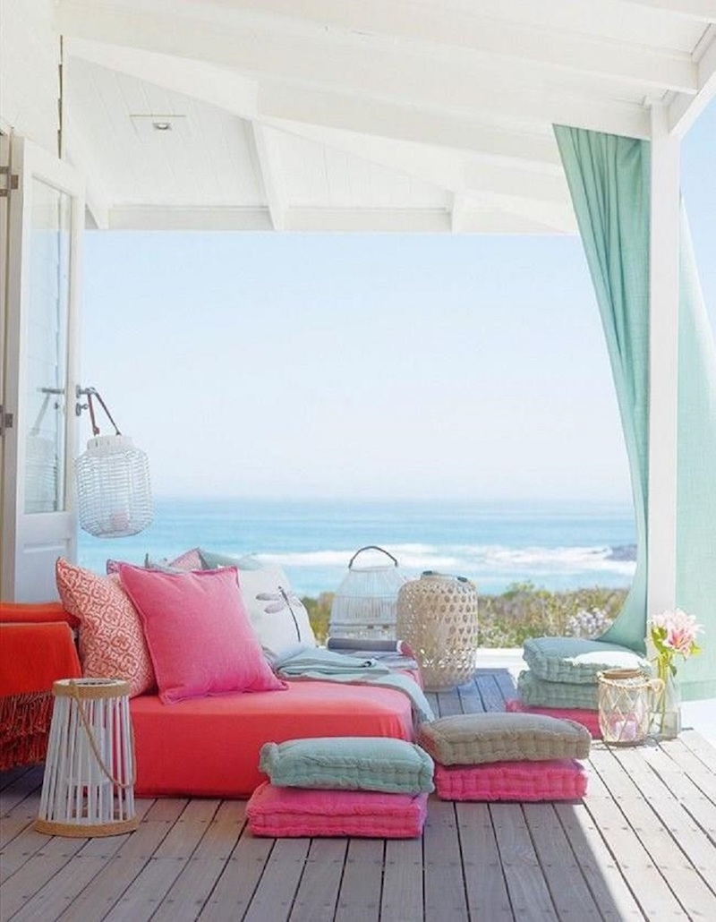 Pink floor cushions on deck overlooking beach