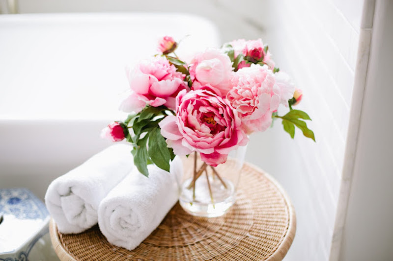 Pink peonies next to bathtub