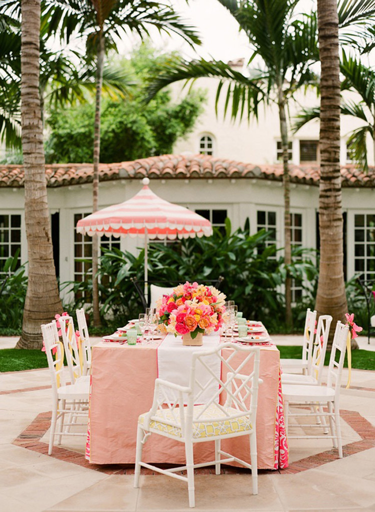 Pink table setting at outdoor patio with palm trees