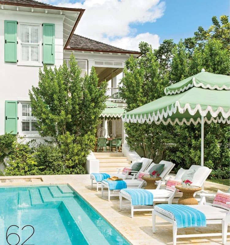 Poolside home with green shutters and two-tier umbrella