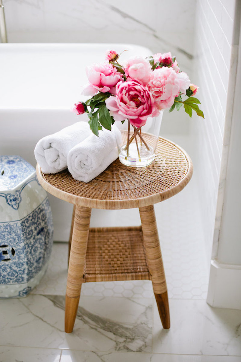 Rattan stool with pink peonies near bathtub