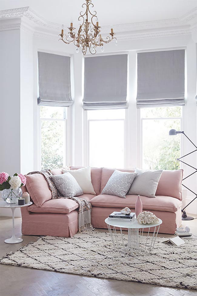 Soft pink sectional sofa with gold chandelier