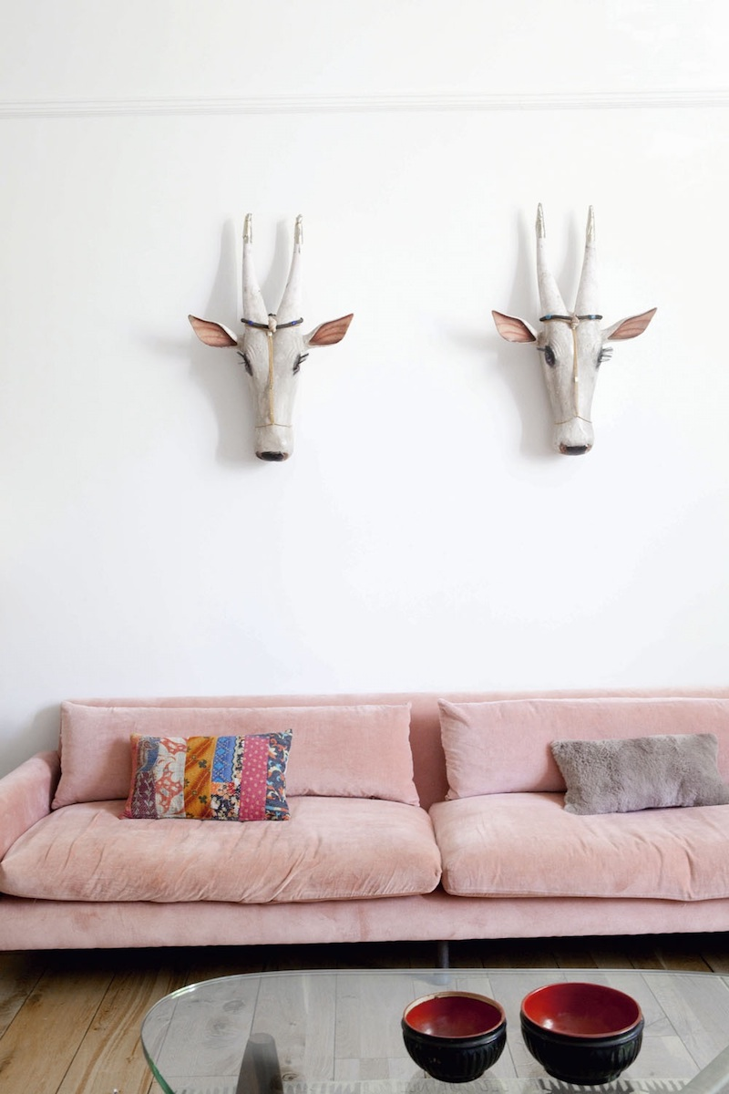 Sunken blush pink sofa with two animal skulls on wall