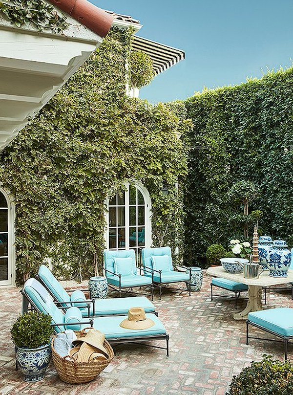 Turquoise lounge chairs near ivy covered house via OKL