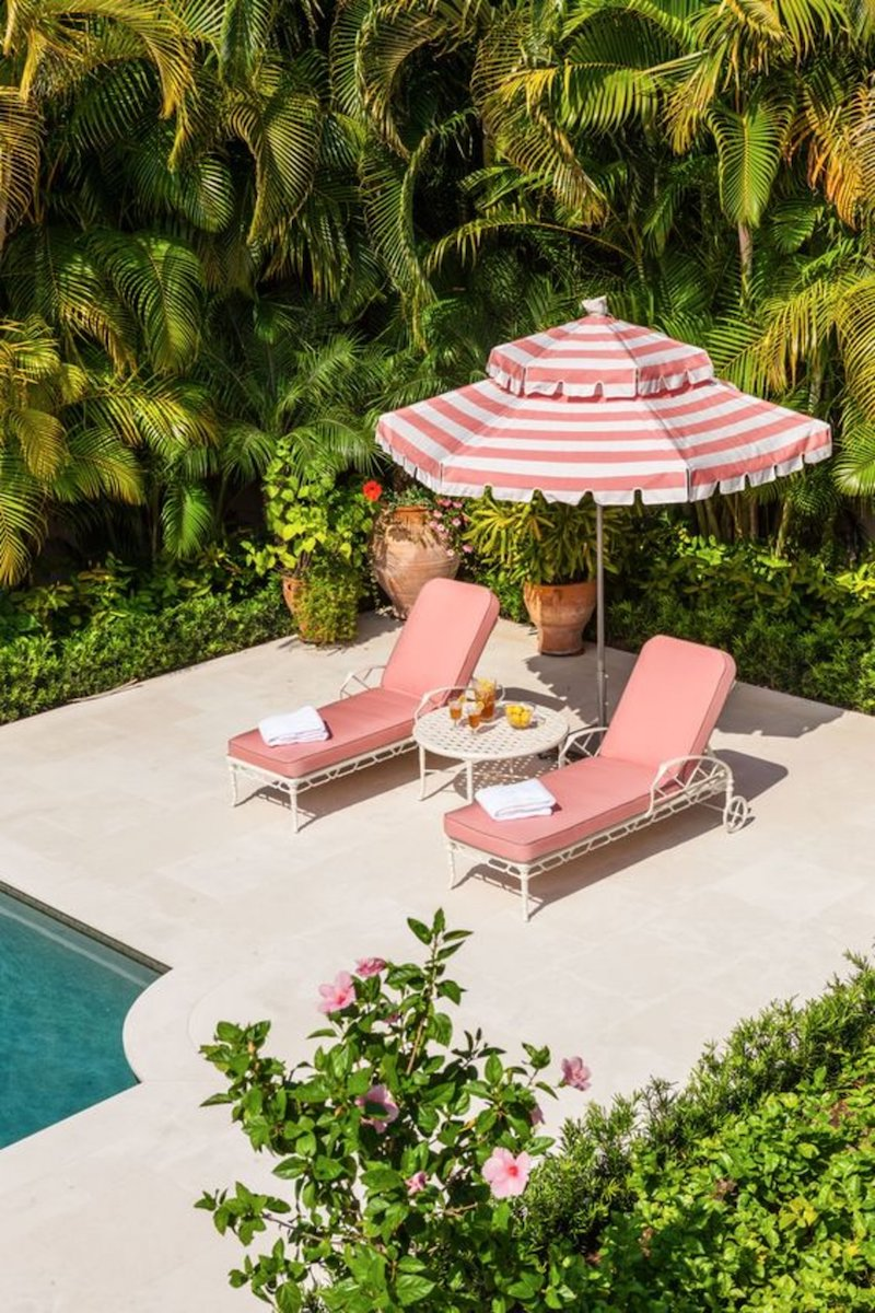 Two pink pool lounge chaises with striped pink umbrella