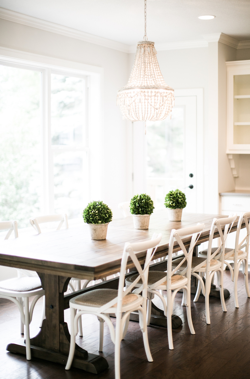 White cross back dining chairs in farmhouse dining room