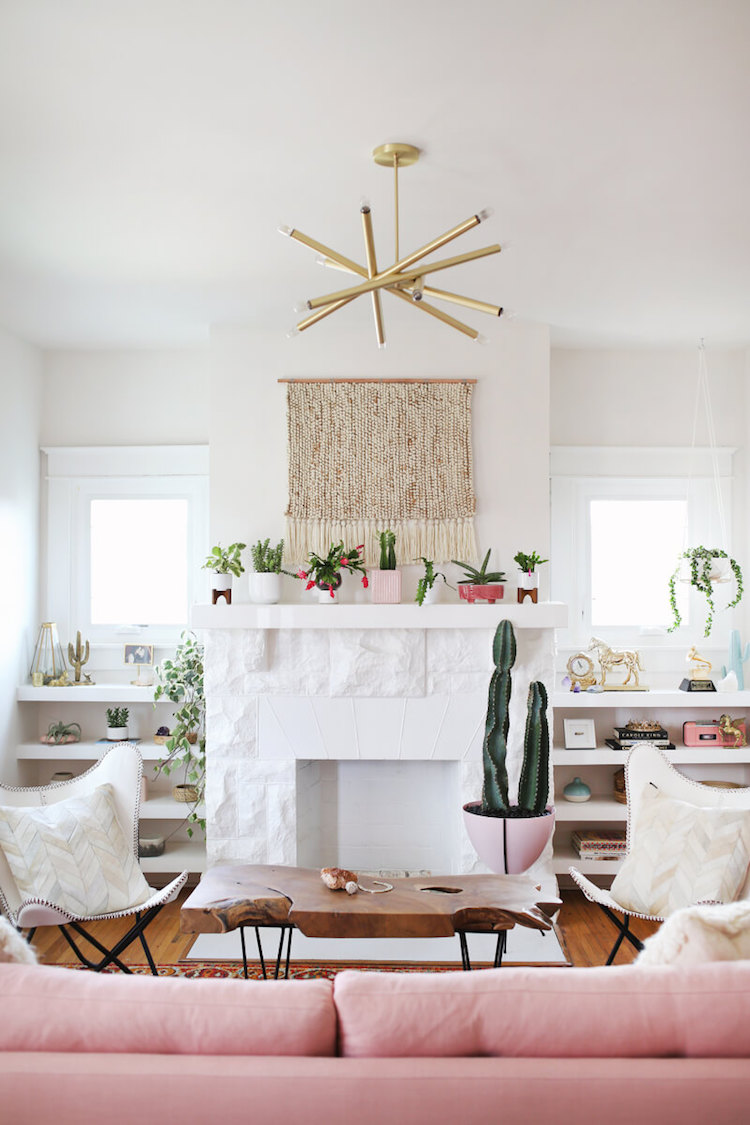 White fireplace with cactus by blush sofa