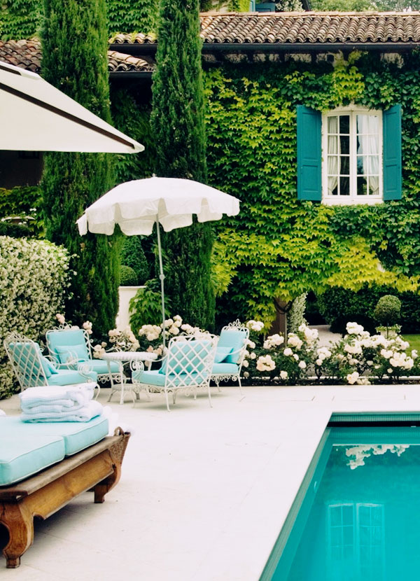White iron outdoor chairs with blue cushions near pool