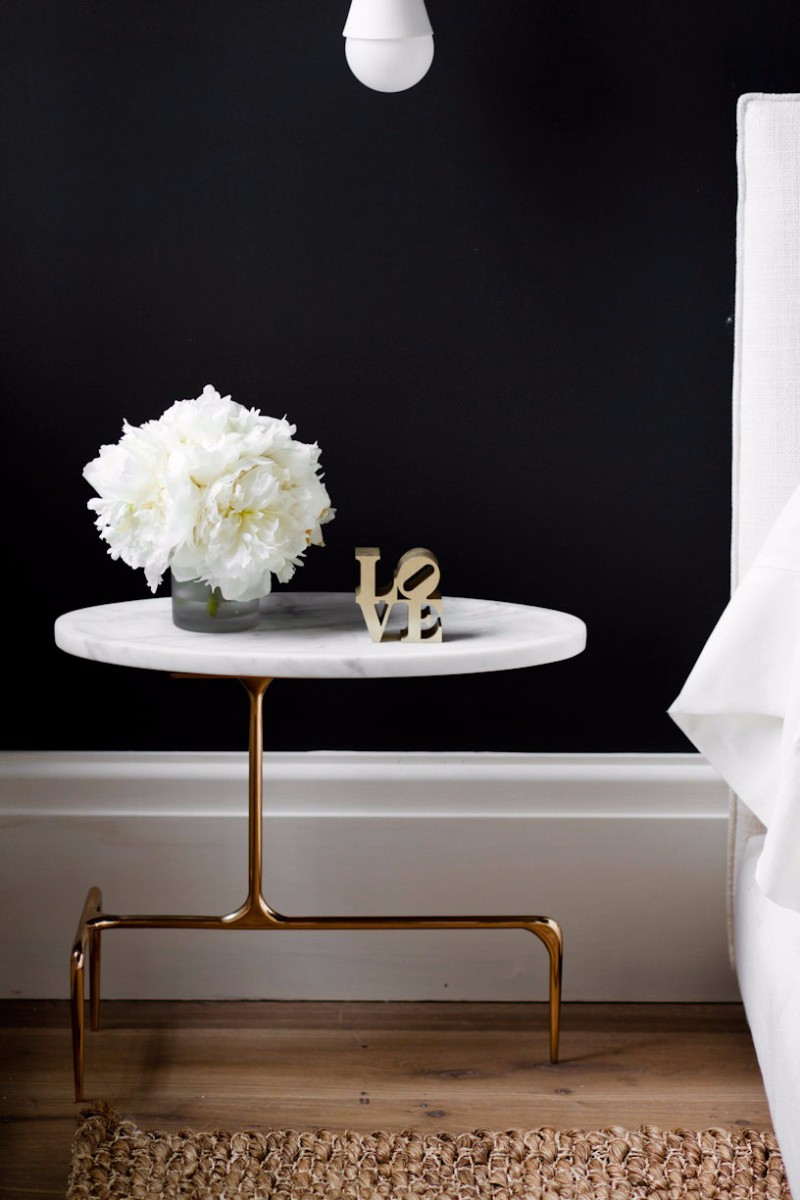 White marble nightstand table with brass base against black wall via Tamara Magel