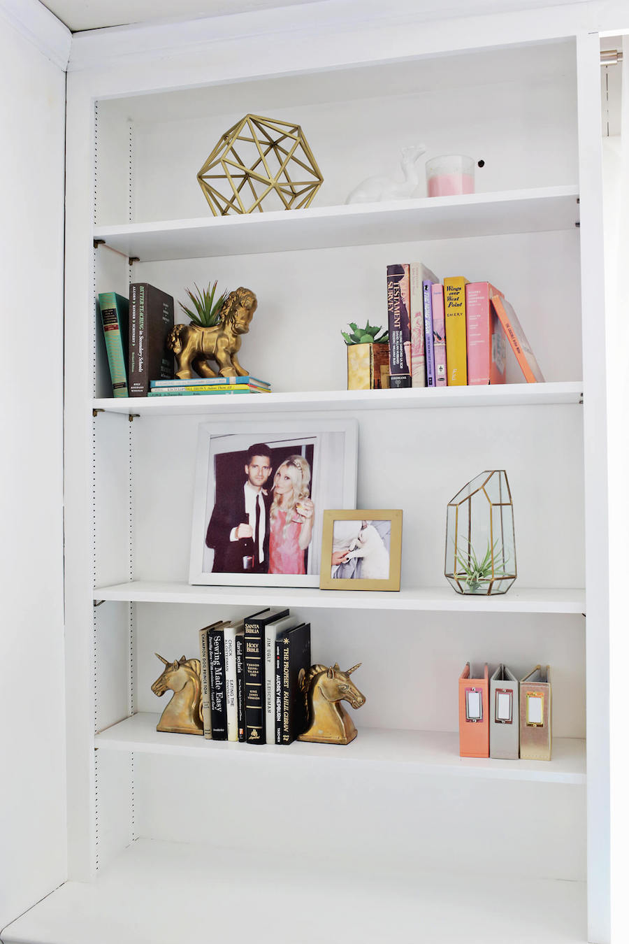 White shelving with gold sculptures