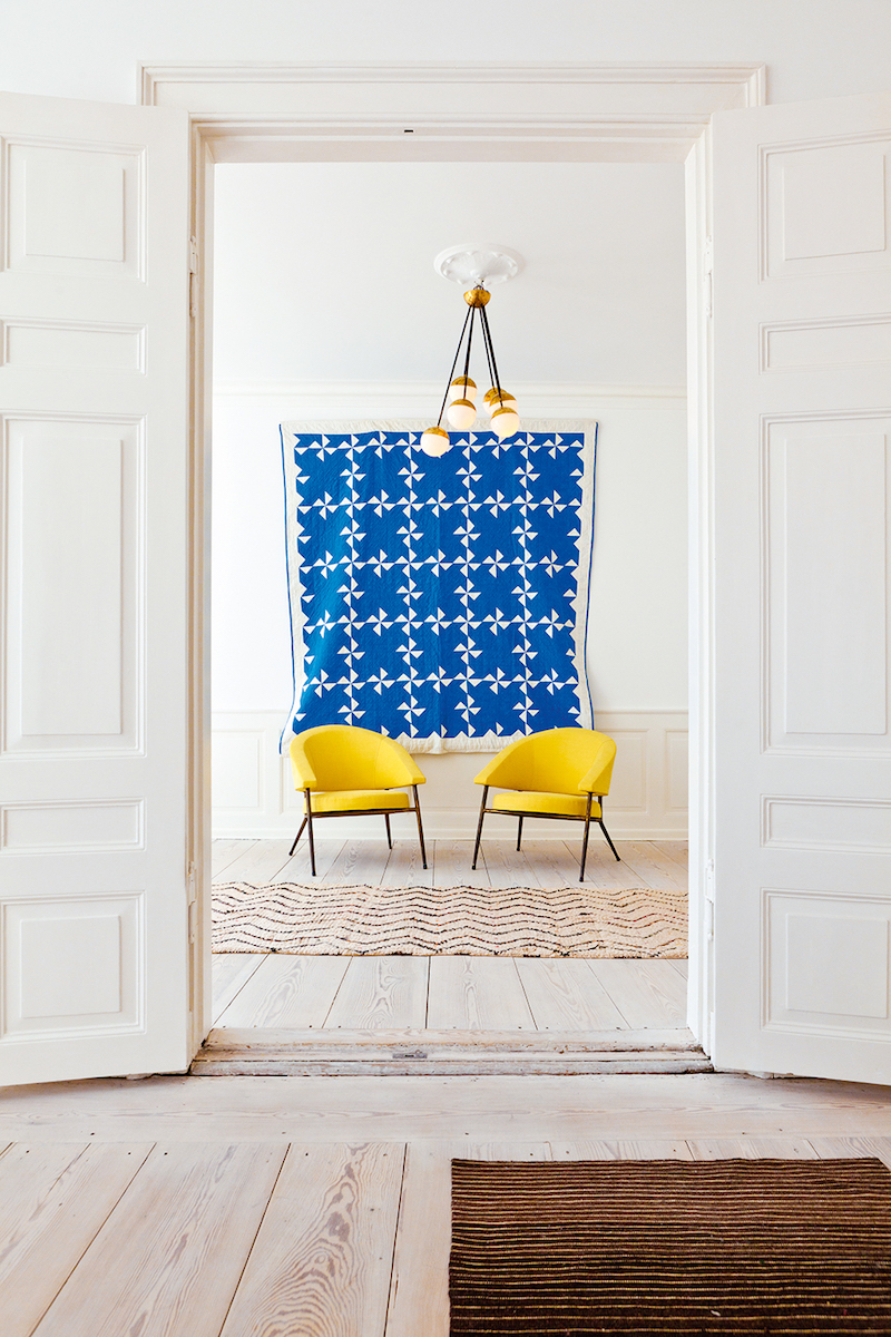 Blue wall art with two yellow accent chairs