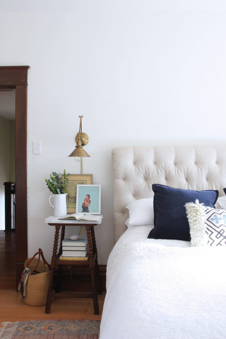 Brass Sconce next to bed in farmhouse home via The Grit and Polish