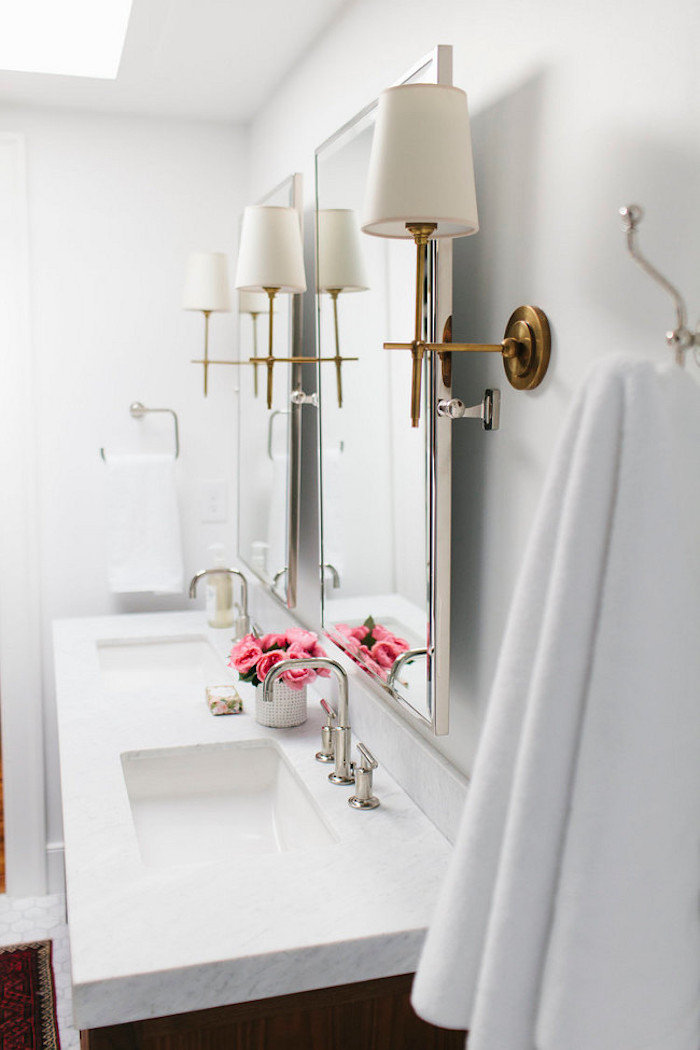 Brass sconces with double vanity in bathroom by Shea McGee Design