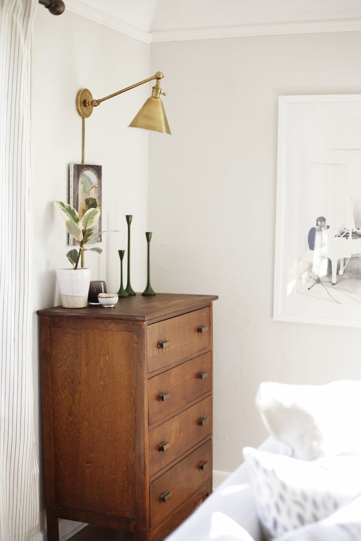 Brass swing arm sconce above wood dresser in bedroom via cocokelley