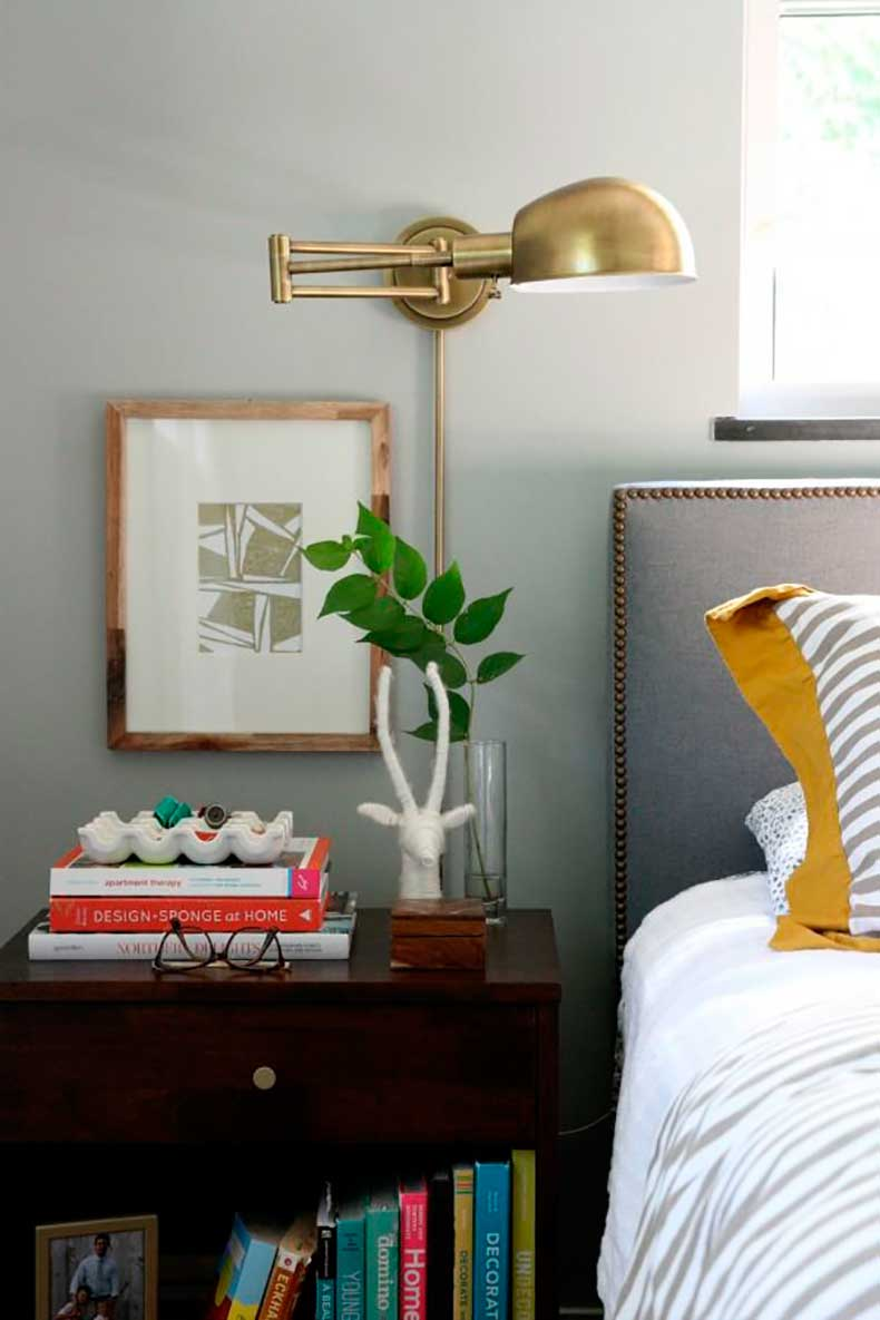 Brass swing sconce in bedroom