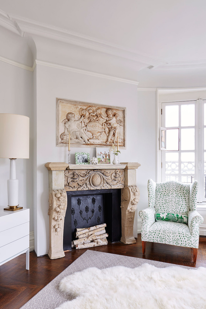 Brown carved fireplace with green wingback chair