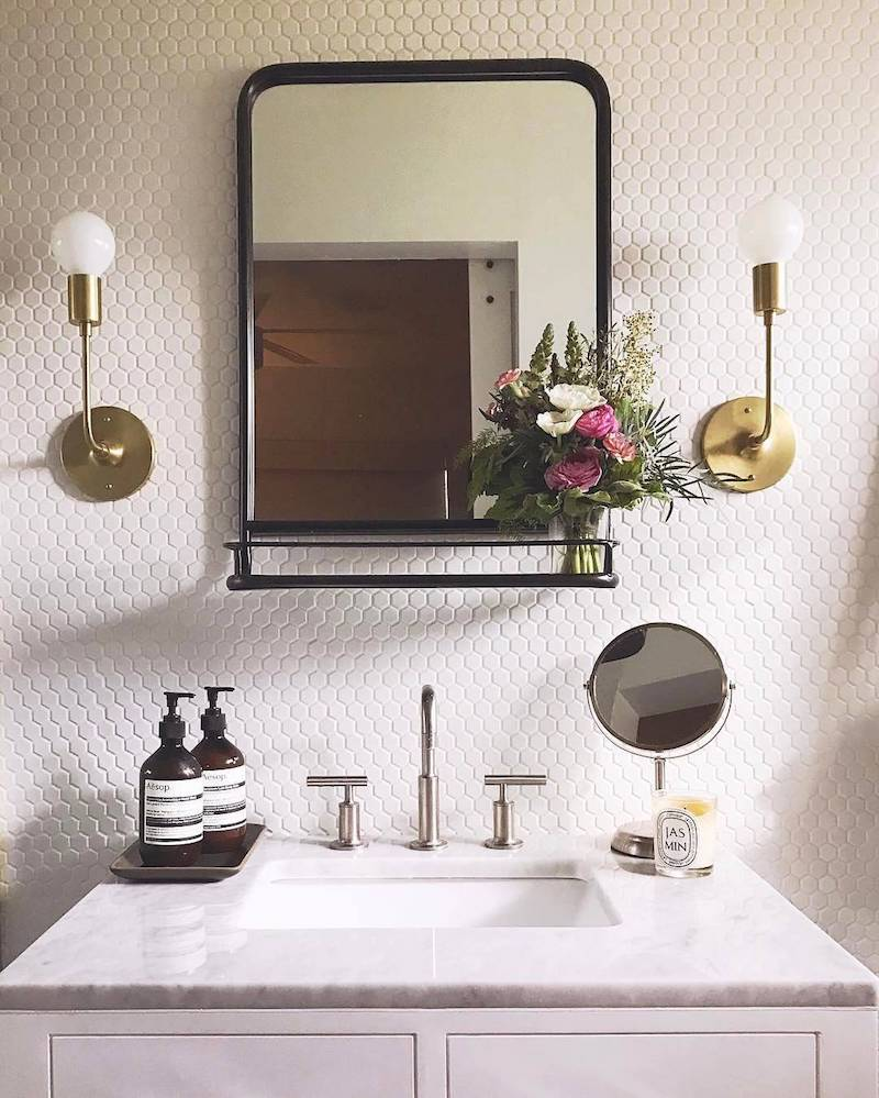 Double brass sconces above bathroom vanity via Schoolhouse Electric