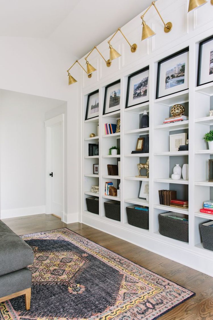Gold arm sconces above bookshelves via Kate Marker Interiors