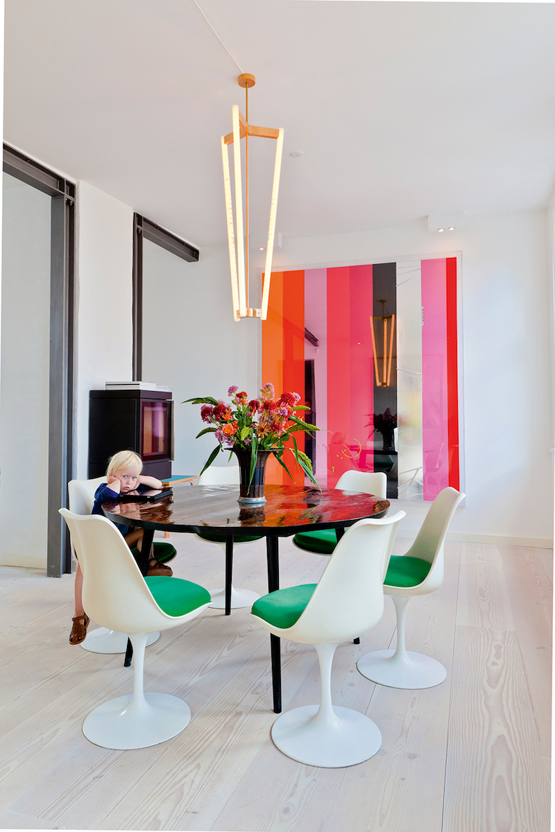 Green cushion white dining chairs with pink striped artwork