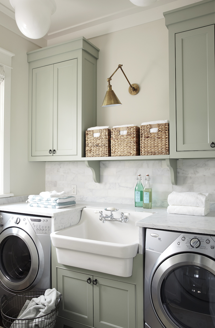 Laundry Room with green cabinets and brass sconce via Urban Grace Interiors