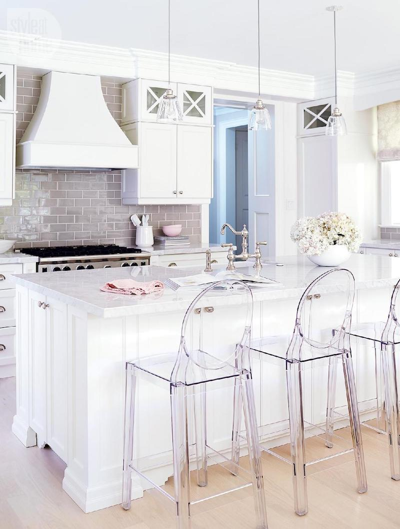 Lucite bar stools in kitchen with gray backsplash