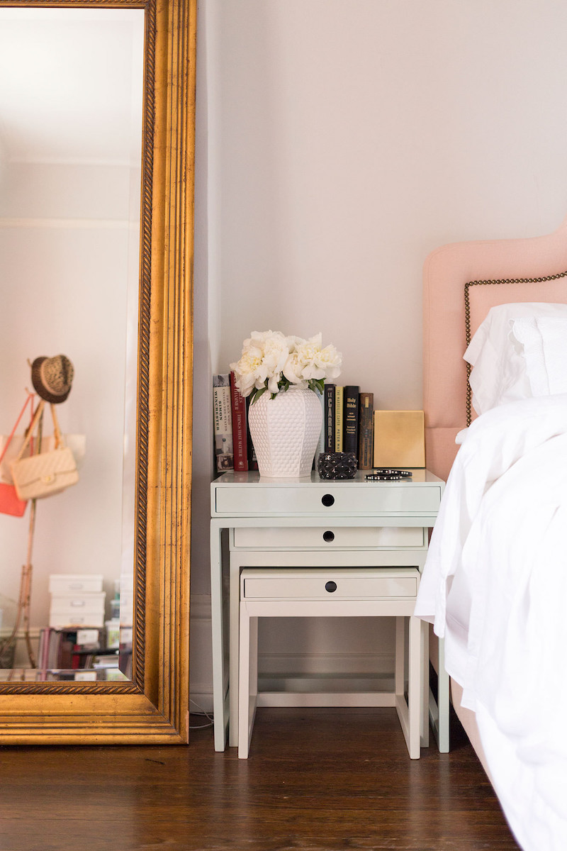 Nesting bedside tables with pink headboard and gold mirror
