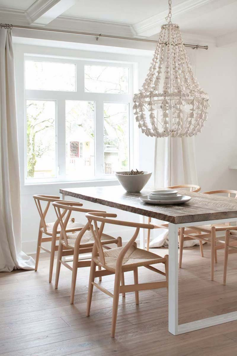 Neutral dining room with wishbone chairs and beaded chandelier via Mount Royal Developments