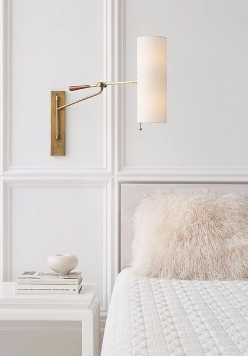 White bedroom with brass wall sconce via Circa Lighting