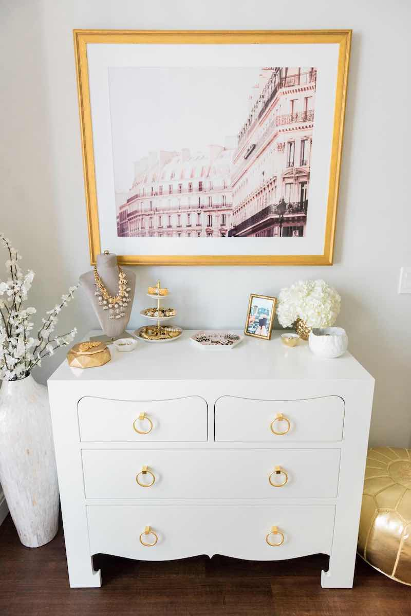White dresser with gold ring pulls and Paris art