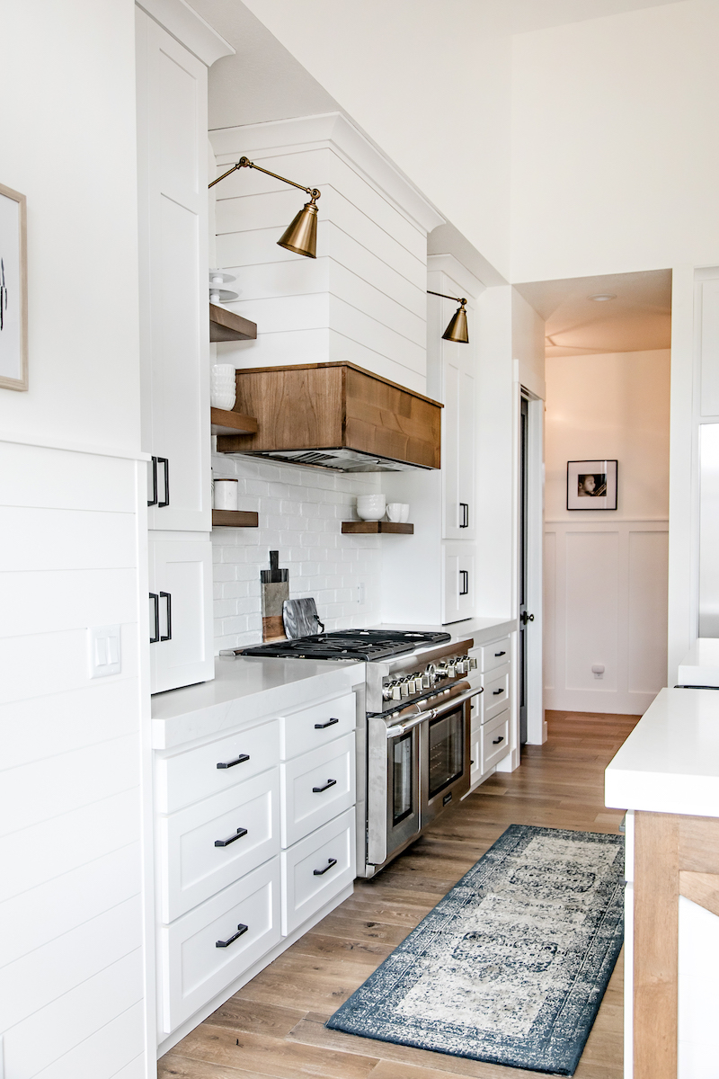 White kitchen with brass overhang sconces via Sita Montgomery