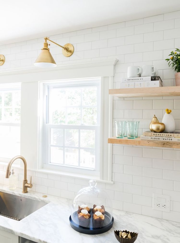 White kitchen with brass sconces and subway tiling and marble counter