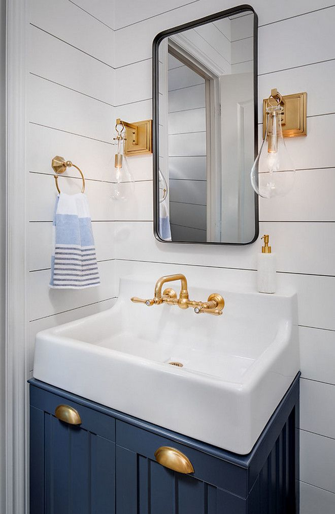 White shiplap bathroom with brass sconces