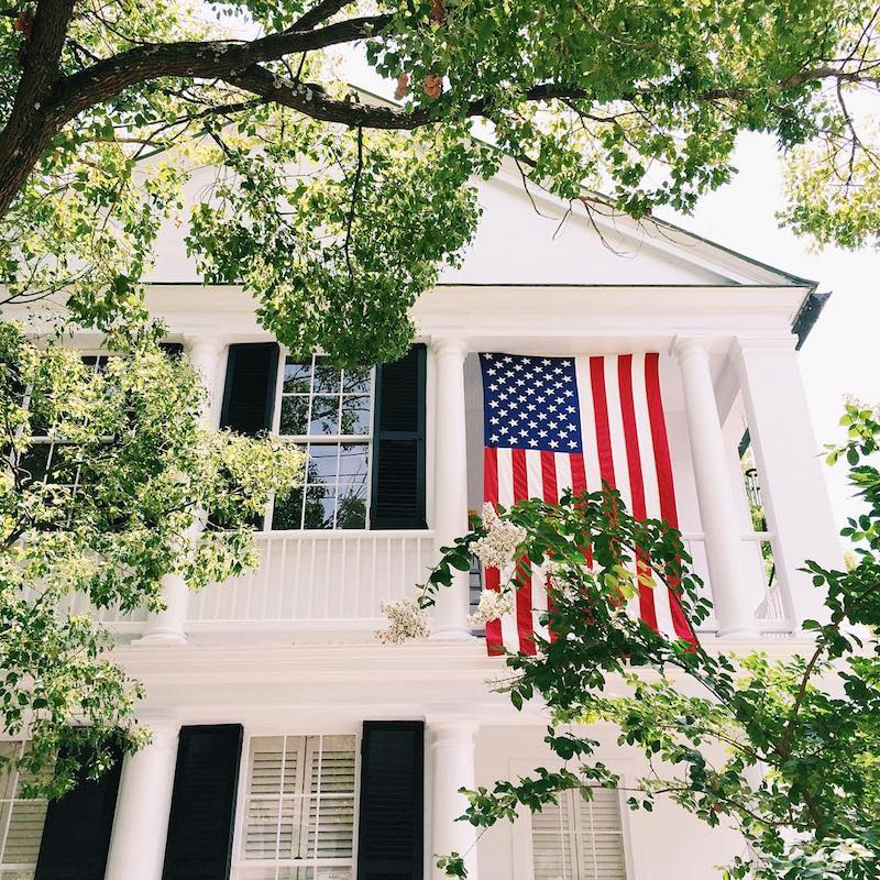 American flag hanging from large white southern style home