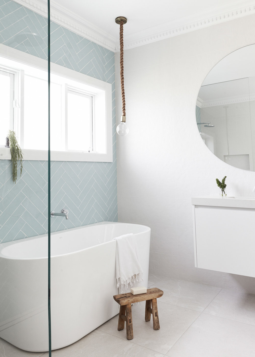 Bathroom with white freestanding tub and rope lightbulb