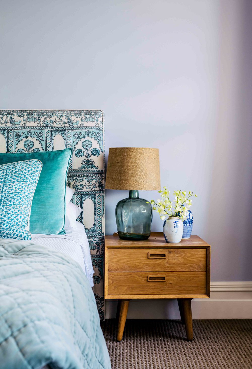 Bedroom with blue fabric headboard and mid-century nightstand