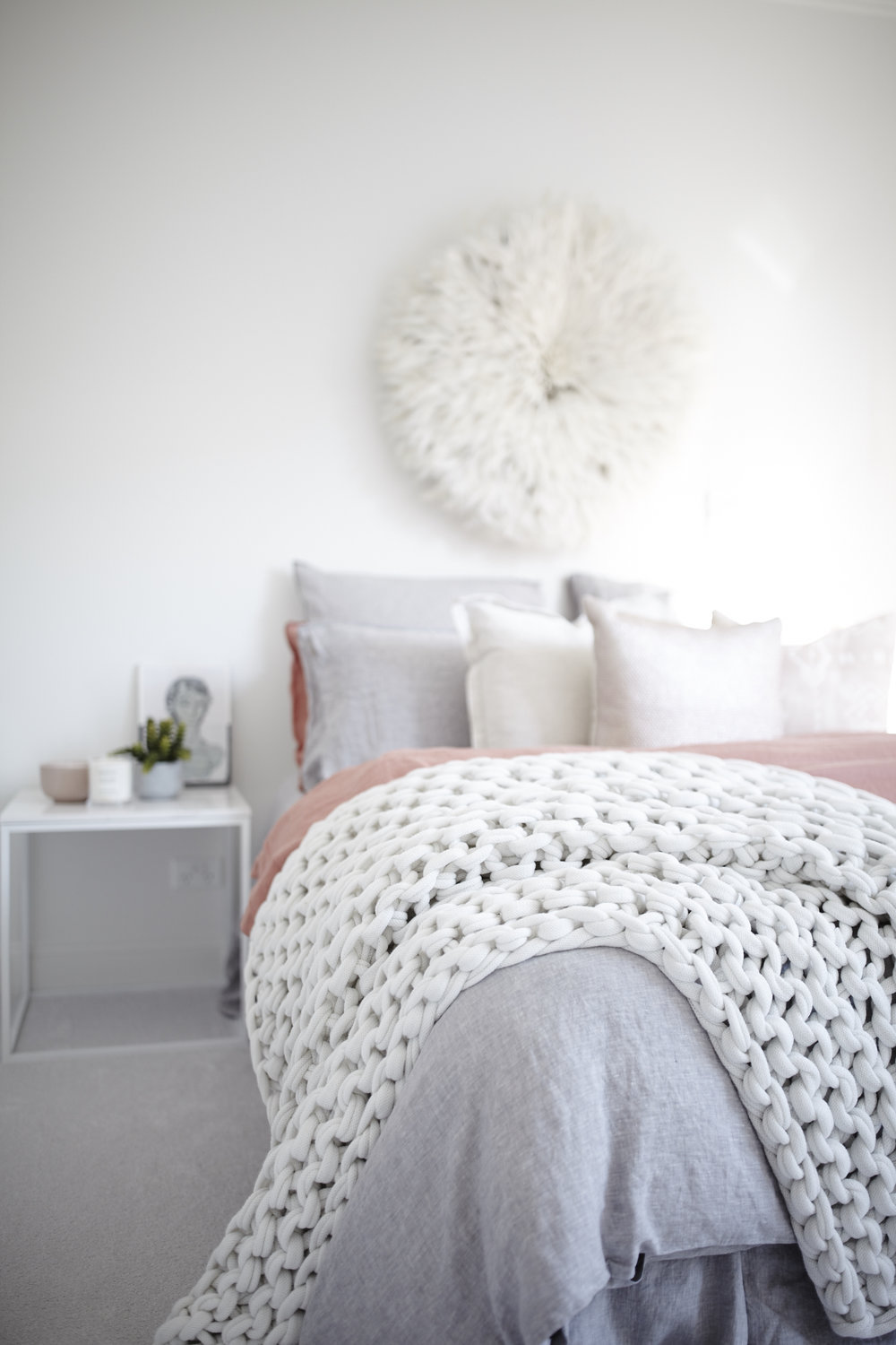 Bedroom with white knit blanket and feather wall decor