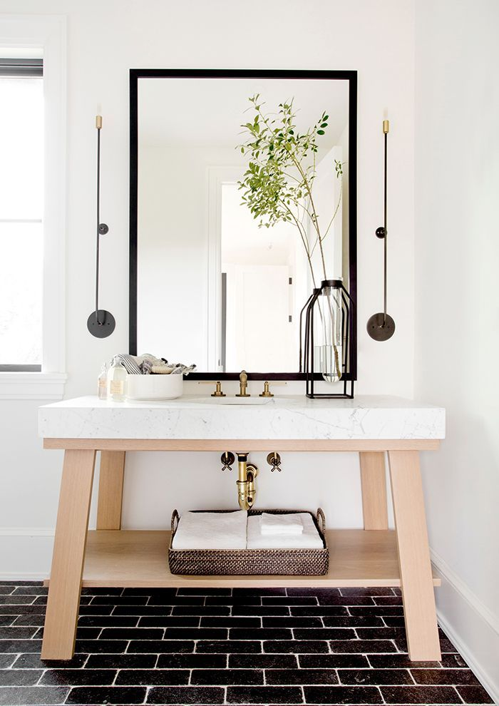 Black floor tiles in well-lit bathroom via Tamara Magel